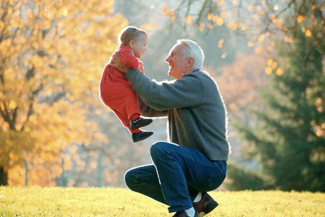 Grandfather Lifting Infant Grandson