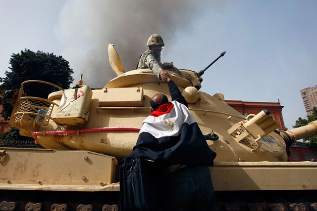 Image: A protester draped in an Egyptian flag climbs atop an army tank to shake hands with a soldier in Cairo